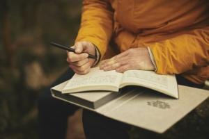 Person schreibt in einem Buch